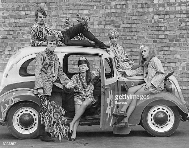 Young men and women pose in and on a car while modeling factorymade versions of Flower Power clothing England