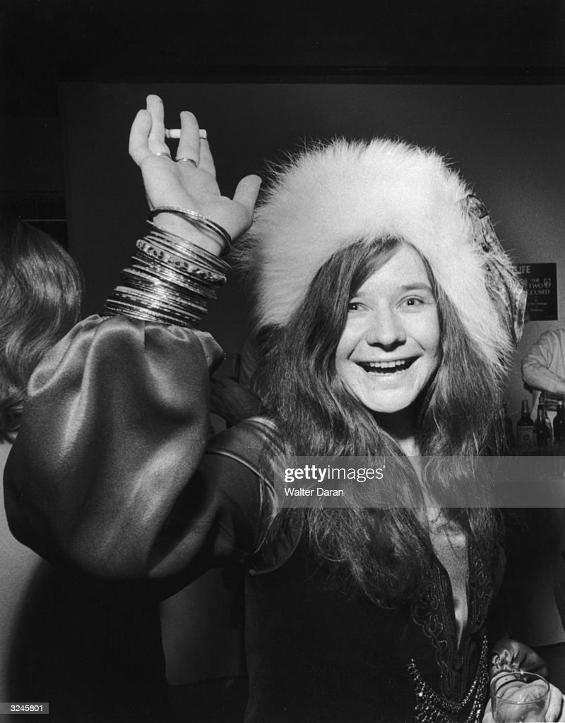 American rock singer Janis Joplin smiles and waves with a cigarette in one hand and a drink in the other while attending a party She wears a fur hat