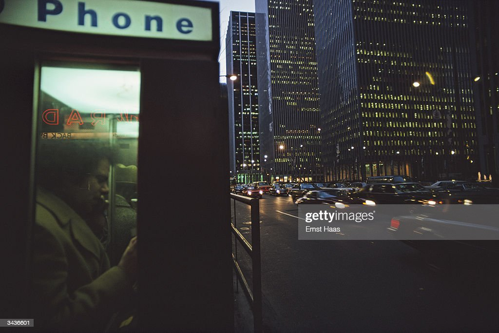 A caller uses a phone box on 6th Avenue, New York, as darkness begins to fall.