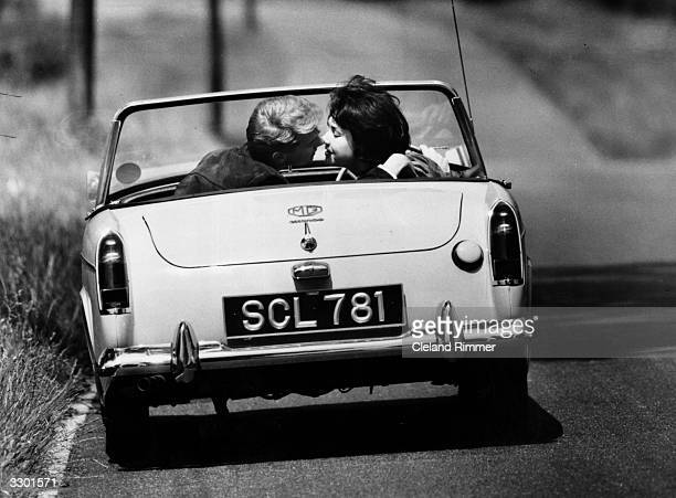 A couple kissing in an MG Midget sports car