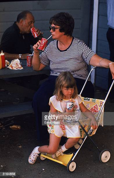 A mother drinks a can of 'cocacola' through a sraw while her young daughter in a push chair similarly enjoys a can of 'fanta'
