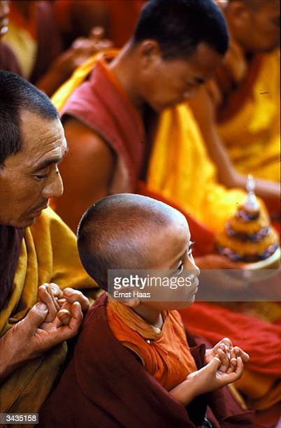 A 'tulku' or reincarnate monk forming the 'mandala mudra' symbol of the universe with all ten fingers during a Buddhist ceremony at the Kalachakra...