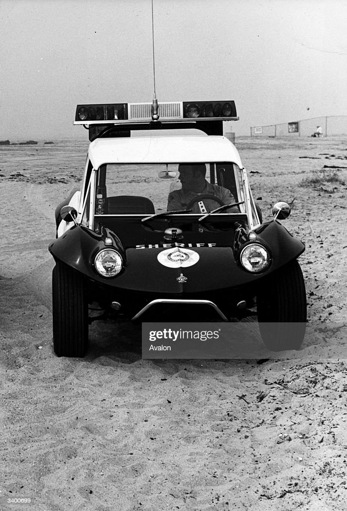 A US sheriff's dune buggy, in use by the Los Angeles Police Force, on Malibu Beach. The buggy is equipped with a two-way radio and flashing light bar and is used for patrolling coastal areas.