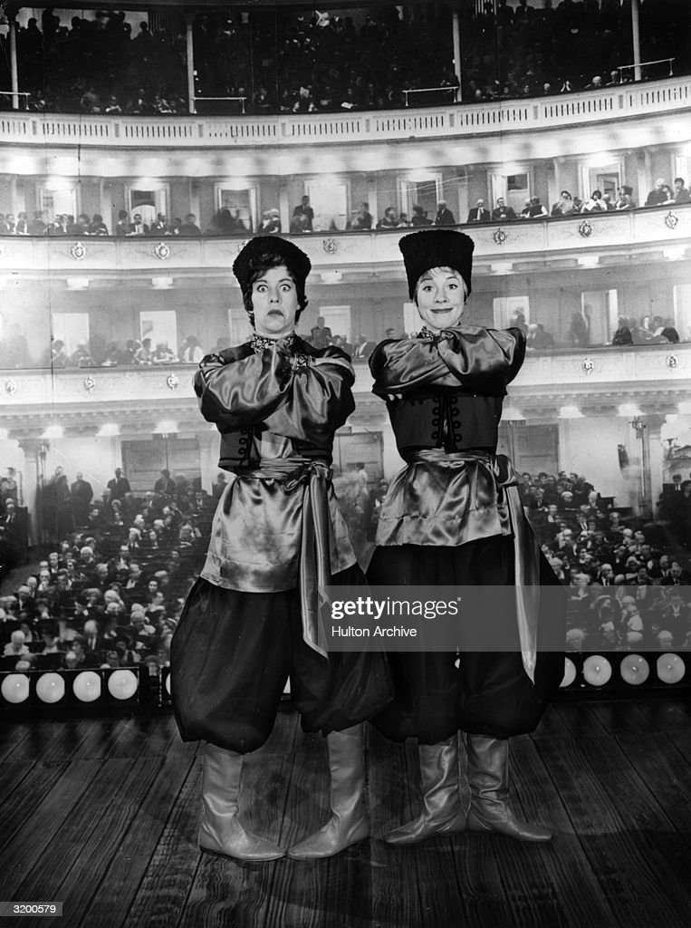 Actors Carol Burnett (left) and Julie Andrews posing in traditional Russian costumes on a stage against a backdrop of a theater audience. Burnett is making a face.