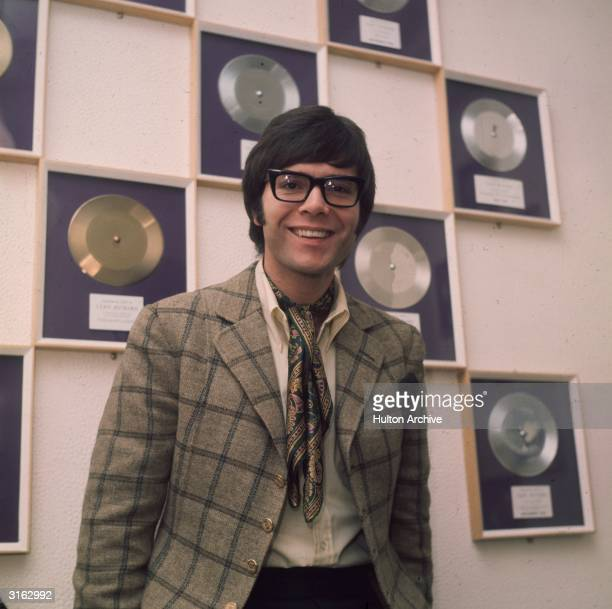 British pop singer Cliff Richard born Harry Webb standing amongst his various disc awards
