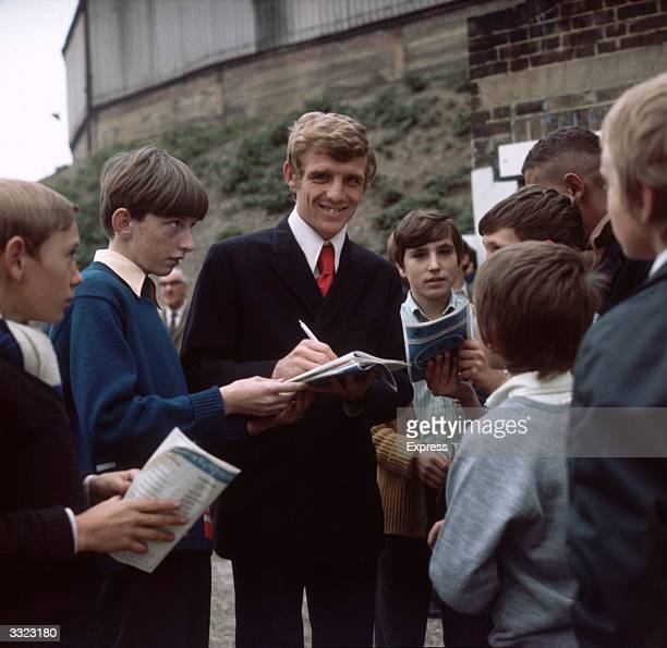 Eamon Dunphy of Millwall Football Club signing autographs for young fans outside the ground