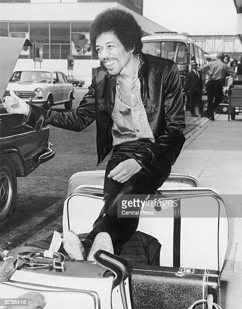 Innovative rock guitarist Jimi Hendrix jokingly thumbs for a lift while waiting with his baggage at Heathrow Airport London