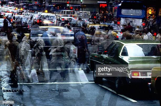 Pedestrians crossing the street amidst traffic in New York City