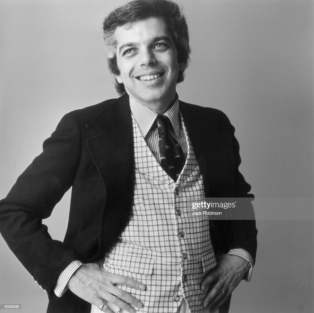 Portrait of American fashion designer Ralph Lauren wearing a checkered vest and striped shirt.