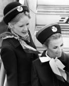 Two BEA air stewardesses fix their smiles in place ready to greet a new planeload of passengers