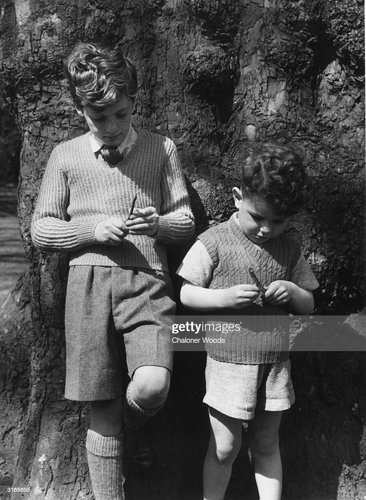 Two schoolboys in shorts and knitted tops lean nonchalantly against a tree and play with a couple of twigs.