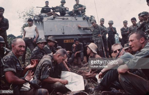 US advisors and South Vietnamese troops gathered in front of a tank during the Vietnam War One American soldier is studying a map