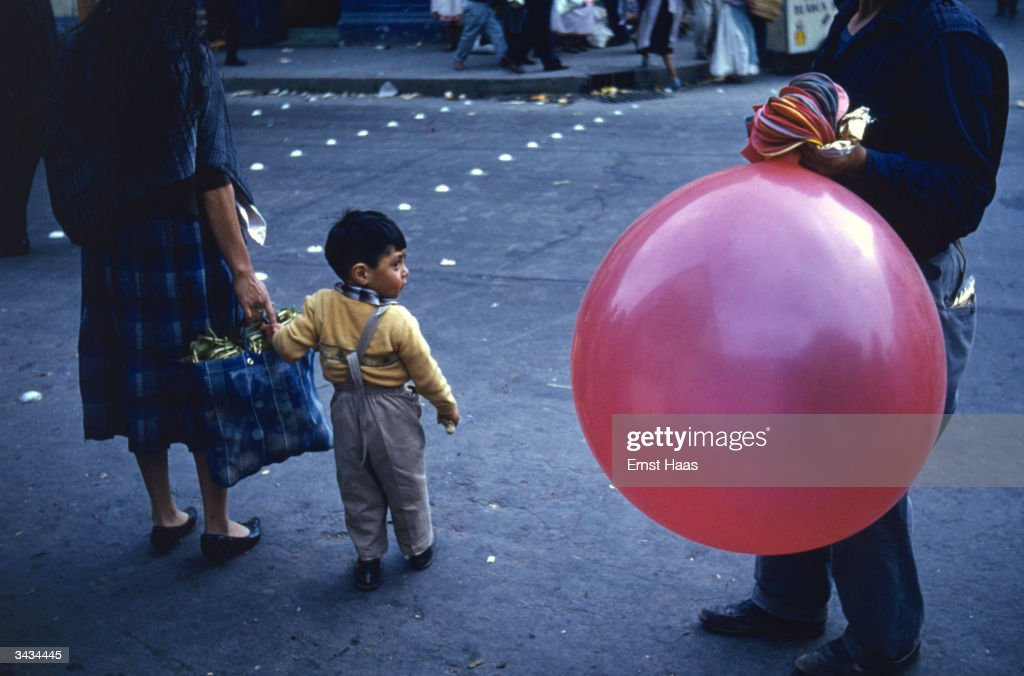 Waiting to cross the street in New York a little boy's attention is caught by a vendor with a large balloon.