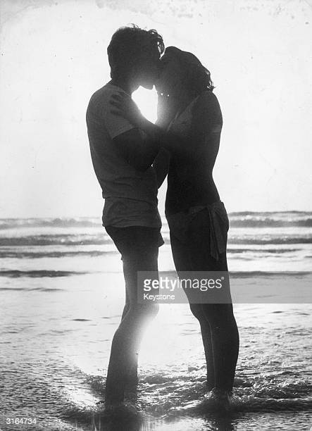 Young lovers stand in the surf as they kiss at sunset