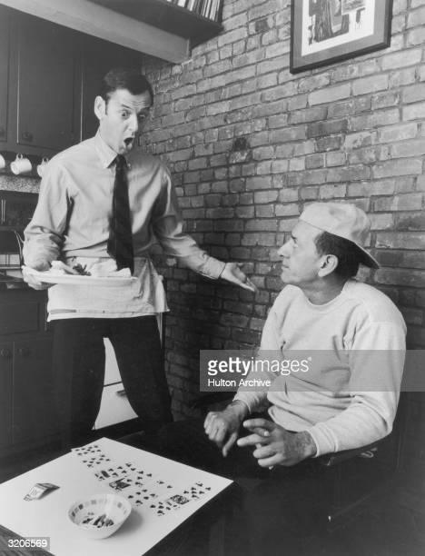 American actor Tony Randall holds a tray of snacks while shouting at American actor Jack Klugman who plays solitaire while holding a cigar in a...