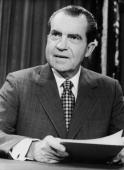 President Richard M Nixon smiles and holds papers while seated at a desk