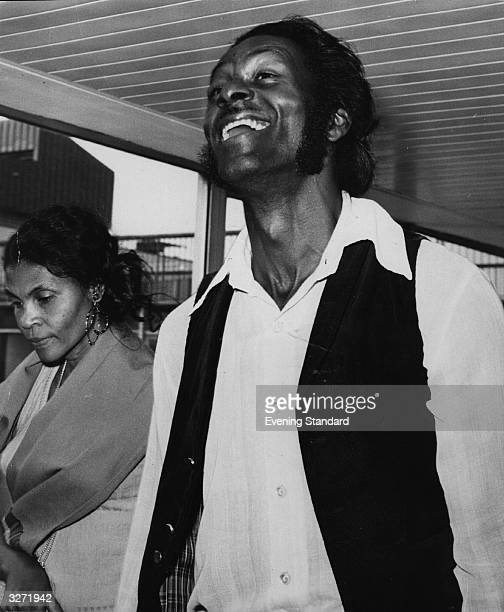 Rock 'n' roll great Chuck Berry in good spirits at Heathrow Airport with his wife