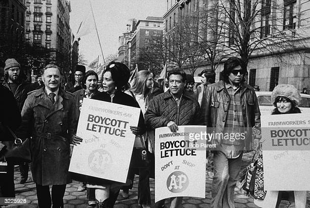 Labor rights leader Cesar Chavez and Coretta Scott King leading a lettuce boycott march down a street in New York City They are holding placards