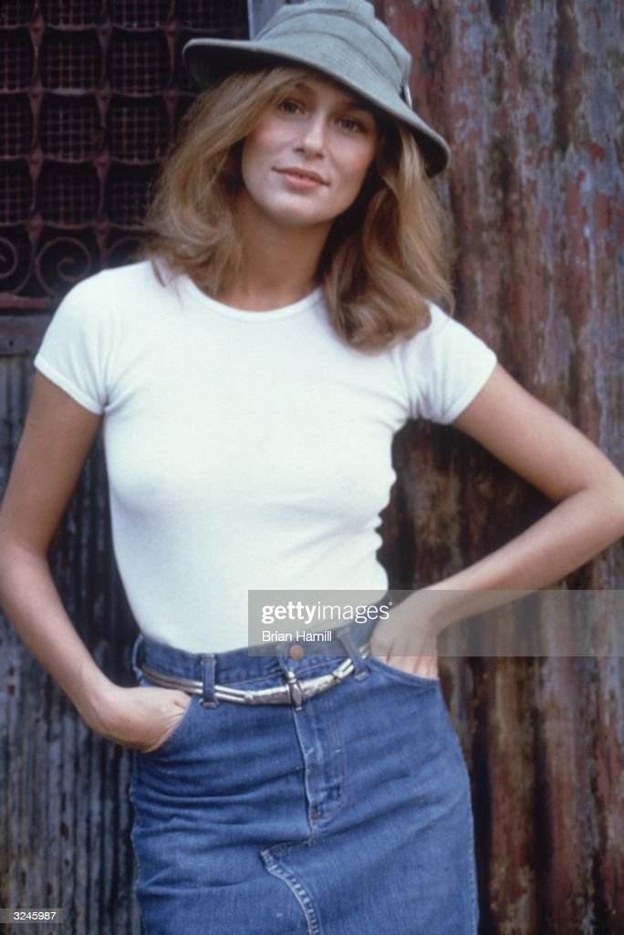 Portrait of American model and actor Lauren Hutton wearing a hat, a white T-shirt and a denim skirt.