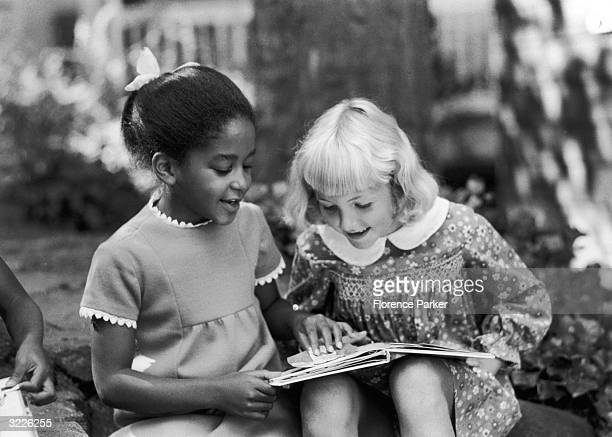 A Caucasian girl and an AfricanAmerican girl sit together outdoors smiling as they read a popup children's book