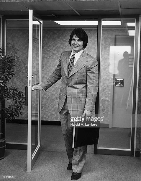 A salesman wearing a plaid polyester suit and carrying a briefcase smiles while walking through the front doorway of an office