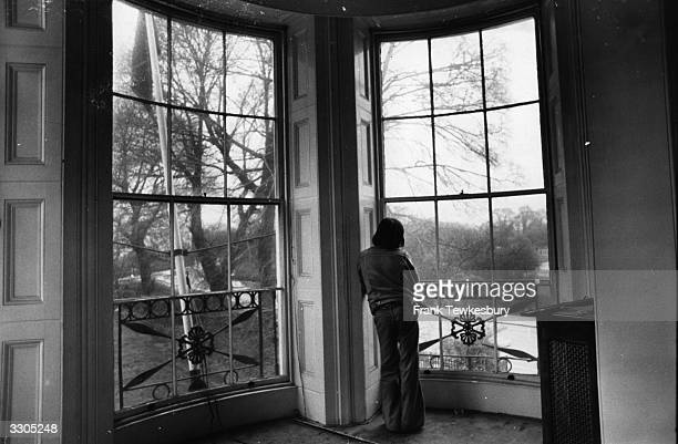 A squatter looking out of the balcony window into Regents Park in a house in Cornwall Gardens London