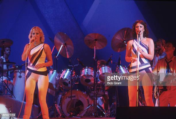 Agnetha Ulvaeus and Frida Lyngstad of the Swedish pop group ABBA perform in spandex costumes on a stage with musicians behind them San Diego