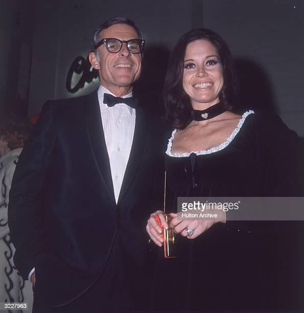 American actor Mary Tyler Moore in a black dress and choker and her second husband American television executive Grant Tinker standing beside each...