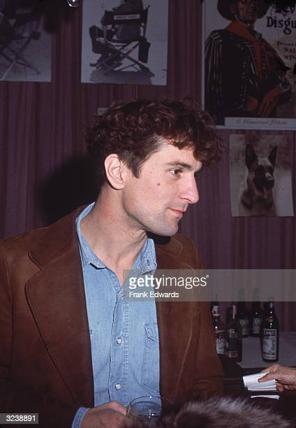 American actor Robert DeNiro wearing a brown suede jacket and a faded denim shirt holds a glass while standing at a bar Movie posters and publicity...