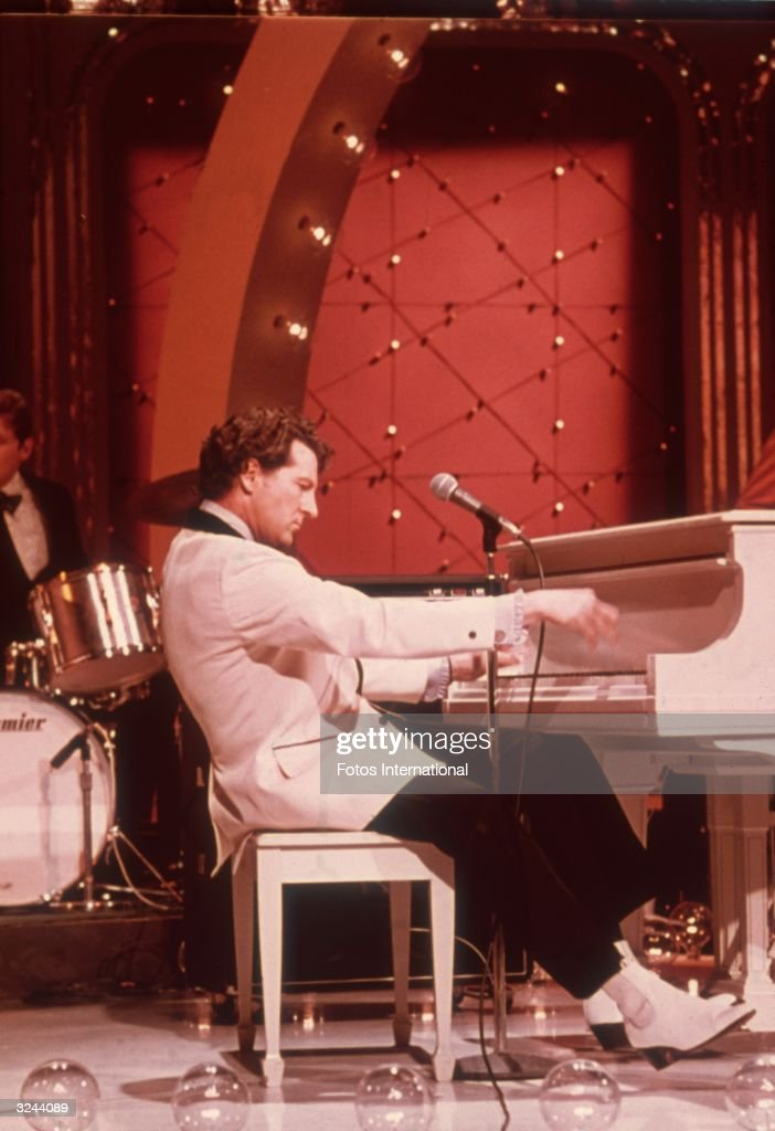 American rock n' roll singer and pianist Jerry Lee Lewis leans back as he plays the piano during a performance on the television program 'Midnight Special'.
