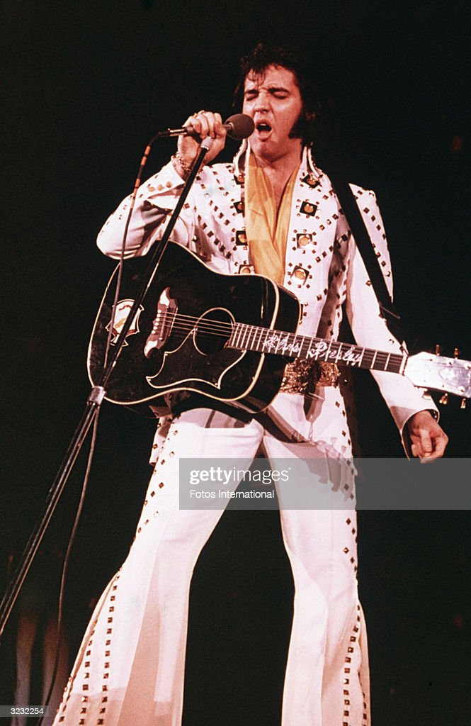 American rock singer Elvis Presley (1935 - 1977), wearing a white rhinestone-studded suit and strapped guitar, singing into a microphone with his eyes closed.