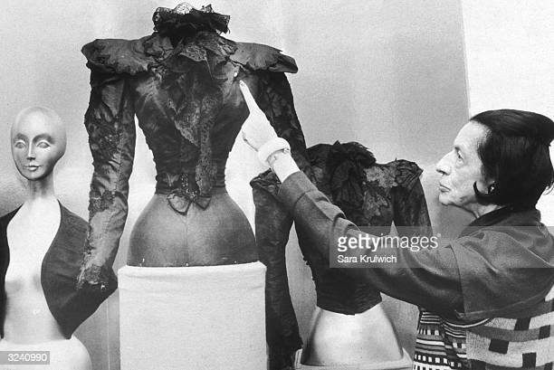Fashion editor and museum curator Diana Vreeland points to a hole in a blouse worn by Empress Elizabeth which was caused by an assassin's bullet on...