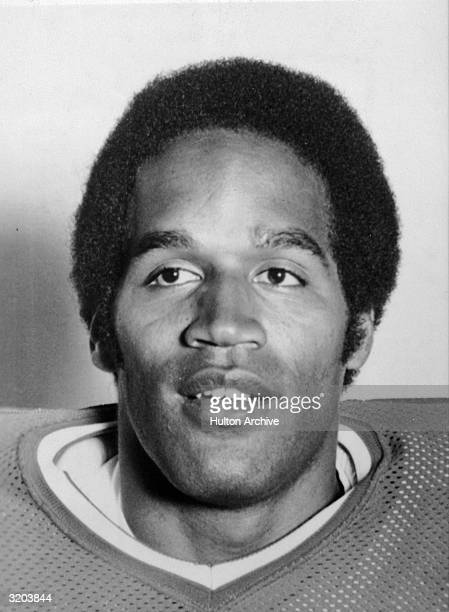 Headshot of American football player O J Simpson smiling in a football jersey and shoulder pads