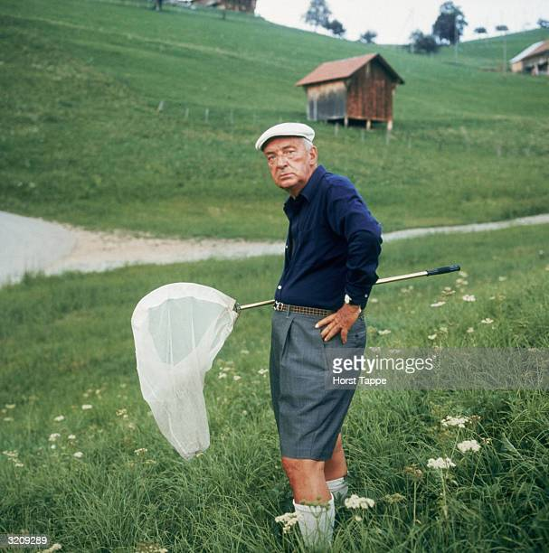 Portrait of Russianborn American writer Vladimir Nabokov standing with a butterfly net outdoors in the hills of Switzerland