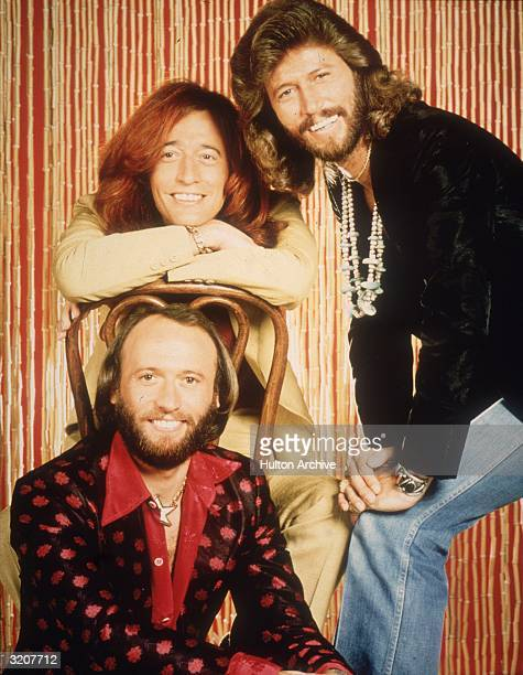 Portrait of the brothers Barry Robin and Maurice Gibb who comprise the pop group The Bee Gees in front of a bamboo curtain