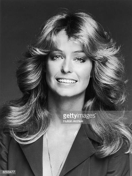 Studio headshot portrait of American actor Farrah Fawcett smiling while wearing a dark blouse and a chain Fawcett has her trademark layered wavy shag...