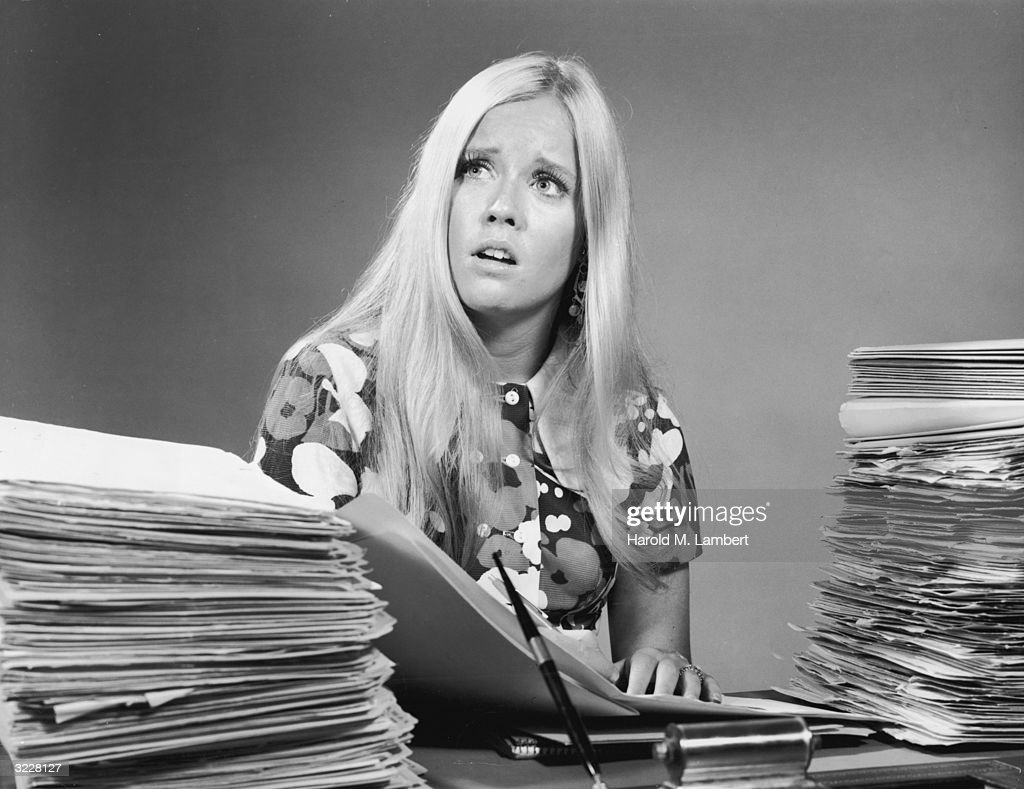 Studio image of a young woman looking overwhelmed as she sits at a desk between two large stacks of paperwork. She wears a brightly patterned shirt.
