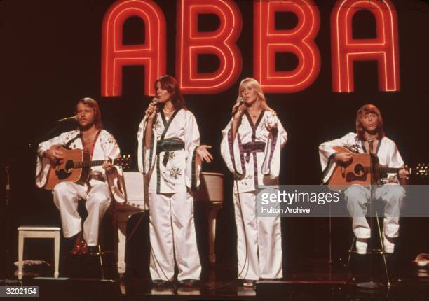 Swedish pop group ABBA wearing similar white Asianinfluenced costumes perform for the television program Midnight Special with a neon 'ABBA' sign in...