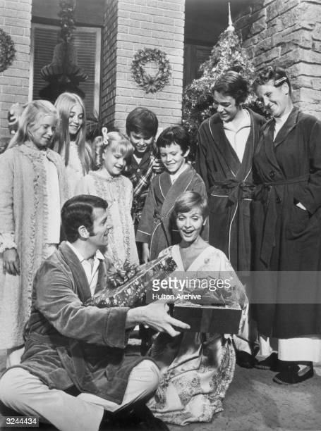 The cast of the television series 'The Brady Bunch' stands and watches American actors Robert Reed and Florence Henderson exchange wrapped Christmas...