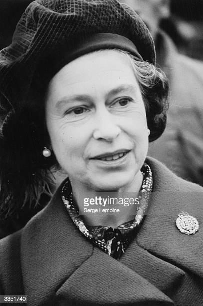 Queen Elizabeth II wearing a velvet beret and a brooch bearing her royal crest