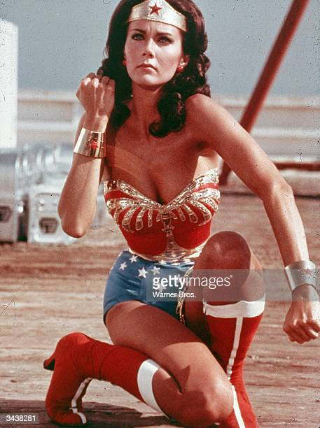 American actor Lynda Carter kneels on the ground and bears her forearm in a still from the television series Wonder Woman