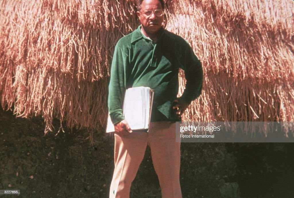 American writer Alex Haley holds a script as he stands in front of a grass hut on the set of the television miniseries 'Roots' based on his novel of...