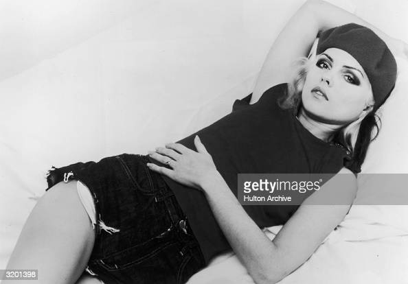 Studio portrait of singer Deborah Harry of the music group Blondie reclining on a bed Harry wears a beret tee shirt and cutoff jean shorts