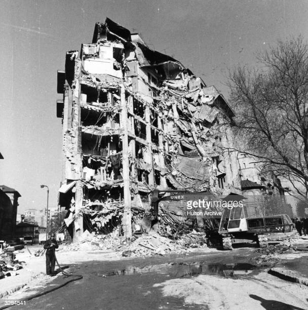 Workmen begin to demolish an earthquake damaged building in University Square Bucharest