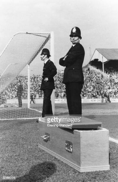 Policemen stand on the edge of the pitch at the Millwall Football Club ground during a game between Millwall and Ipswich Town Beside them is a coffin...