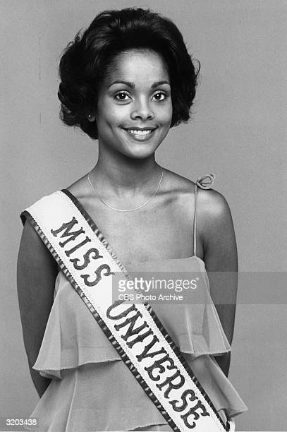 Portrait of Janelle Commissiong Miss Universe 1977 smiling while wearing a sash over her gown