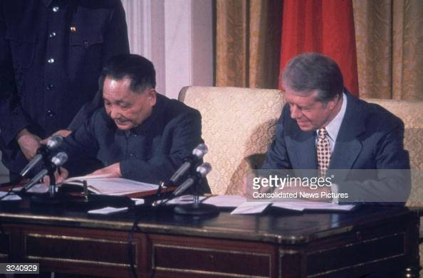 American president Jimmy Carter and Chinese Communist leader Deng Xiaoping sign papers to establish formal diplomatic ties between the US and China...