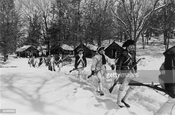 A band of men dressed as colonial soldiers march past a row of reconstructed log cabins in Valley Forge National Historical Park Pennsylvania The...
