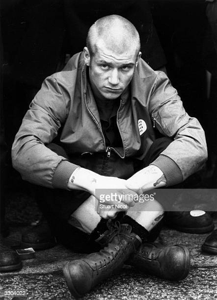 A skinhead sitting crosslegged during a British Movement rally in Notting Hill London