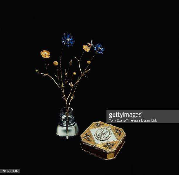 A sprig of blue cornflowers created by the House of Fabergé along with a jewelled snuffbox topped with the monogram of Tsar Nicholas II in diamonds